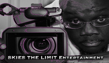 Image of a video camera outlined in purple sitting on a table next to Anthony Amos' face leaning in next to it. He is a dark skinned bald man wearing glasses and looking straight forward.